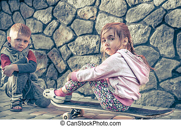 little girl and boy playing on skateboard, against the backdrop of stone wall, concept of childhood friendship