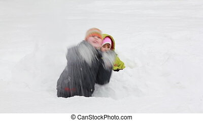 little girl and boy sit among snow, he throws it to chamber in winter morning