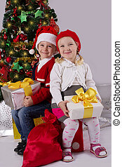 Little girl and boy sitting with gift under Christmas tree