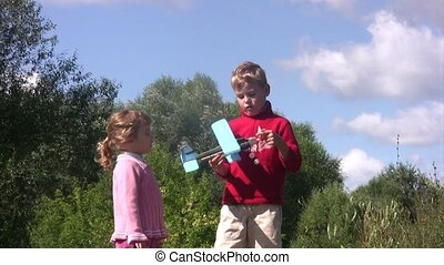 Little girl and boy stand in park, at boy in hands the toy plane.