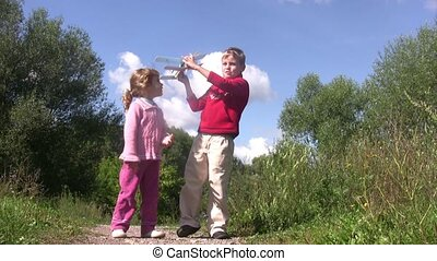 Little girl and boy stand in park, boy launch toy plane.