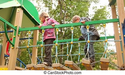 Little girl and boy sway on hang down steps at playground