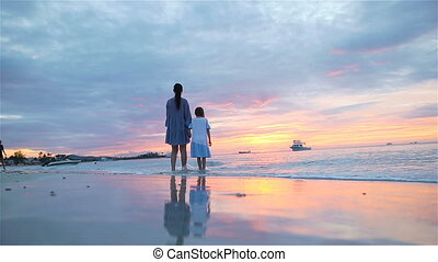 Little girl and daddy silhouette in the sunset at the beach...