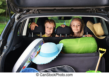 little girl and her brother sitting in car