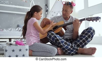 Little girl and her caring father playing the guitar