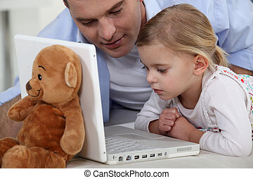 Little girl and her dad using the laptop