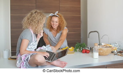Little girl and her daughter baking cookies at home, reading recipe on laptop.