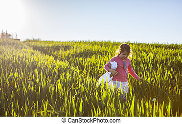 Little girl and her doll walking through green cereal field at sunset