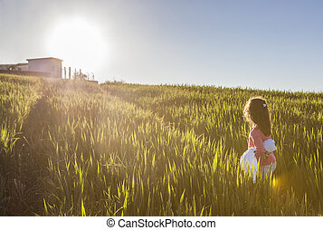 Little girl and her doll walking to the sun through green...