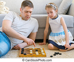 Little girl and her father playing checkers.