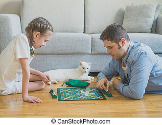 Little girl and her father playing scrabble board game.