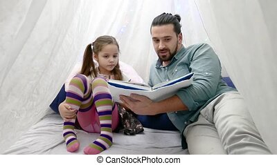 little girl and her father reading a book together -...