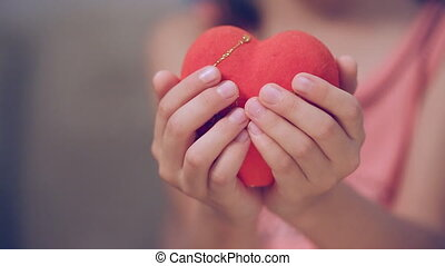 Little girl and her mother holding a heart