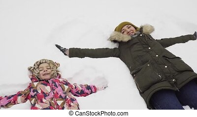 Little girl and her mother makes a snow angel
