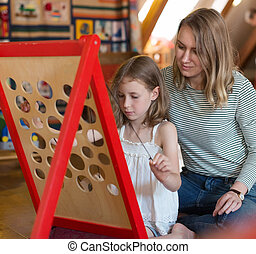 Little girl and her mother playing in educational game.