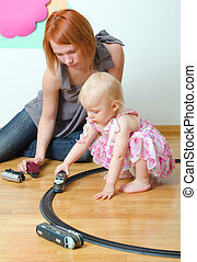 Little girl and her mother playing with railway sitting on the floor