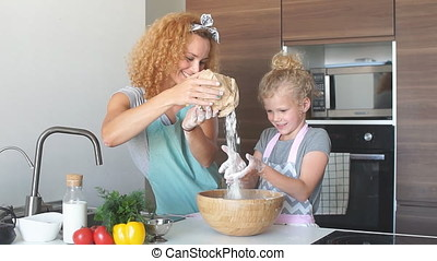 Little girl and her mother sprinkling flour into a bowl and smiling while baking