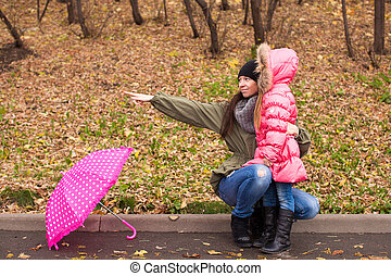 Little girl and her ??mother walking with umbrella on a rainy day