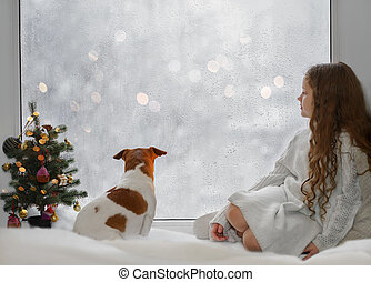 Little girl and her puppy jack russell sitting by the window
