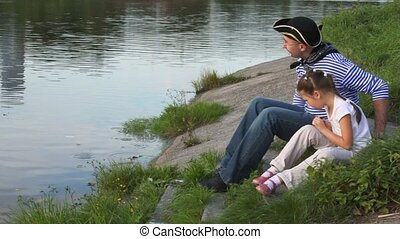 little girl and man in pirate costume sits on coast