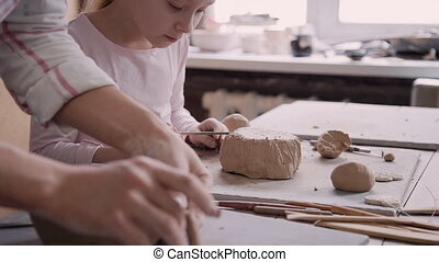Little girl and man working with clay in pottery studio -...
