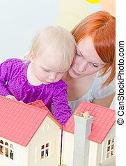 Little girl and mother playing with dollhouse.