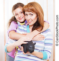 Little girl and mother saving money in a piggybank