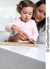 Little girl and nanny making a puzzle