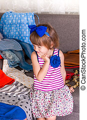 Little girl and new clothes. Child choosing her clothes. View a lot of wardrobe. Thinking.