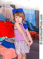 Little girl and new clothes. Child choosing her clothes. View a lot of wardrobe.