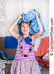 Little girl and new clothes. View a lot of wardrobe. Clothes on the head. Joy, play.