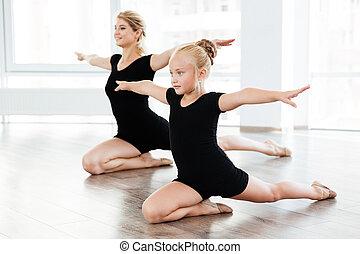 Little girl and woman ballerina dancing together in ballet school