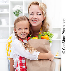 Happy little girl and woman with the groceries bag wearing aprons