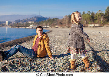 Little girl and young father at the beach on a sunny winter day
