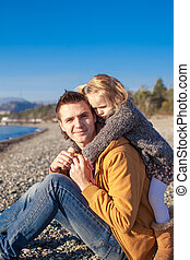 Little girl and young father at the beach have fun on a sunny winter day