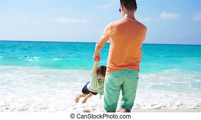 Little girl and young father having fun during tropical beach vacation. SLOW MOTION