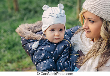 Little girl and young mother over a nature background