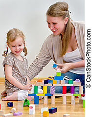 Little girl and young woman having fun playing with building blocks on the floor