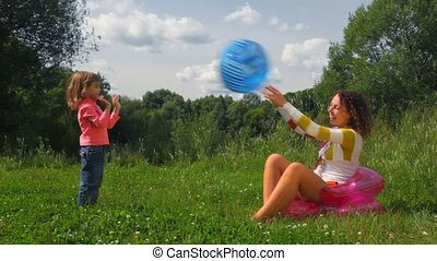 little girl and young woman playing with inflatable ball outdoors