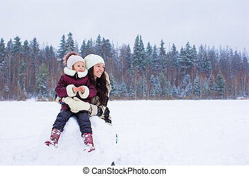 Little girl ang happy mom enjoy winter snowy day - Happy...