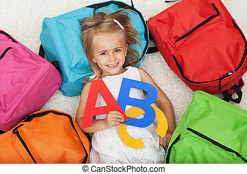 Little girl anxious to go to school - lying on the floor among colorful school bags