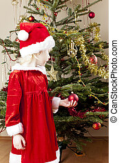 little girl as Santa Claus by Christmas tree