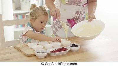 Little girl assisting Mum with the baking holding onto the...
