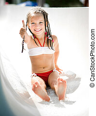 Little girl at aquapark - Little girl on water slide at ...