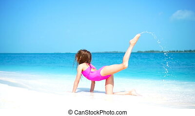 Little girl at beach having a lot of fun in shallow water on the beach