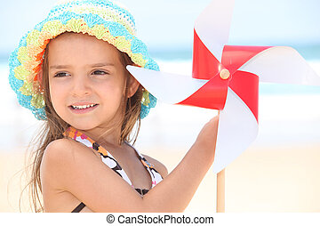 little girl at beach with toy windmill