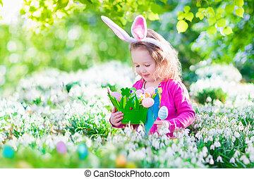 Little girl at Easter egg hunt - Adorable curly toddler girl...