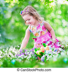 Little girl at egg hunt - Adorable curly toddler girl in a ...