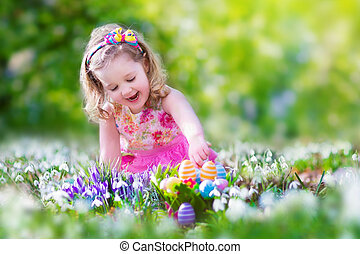 Little girl at egg hunt - Adorable curly toddler girl in a...