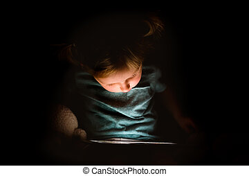 Little girl at home at night watching something on tablet.